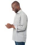 Afrikansk man som använder hans mobiltelefon Arkivbild