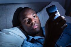 Afrikansk man som anv?nder mobiltelefonen arkivfoton