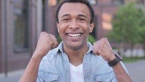 Afrikansk man som firar utomhus- framgång stock video