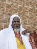 Afrikansk man som framme står av hans hus, åttio gamla år fotografering för bildbyråer