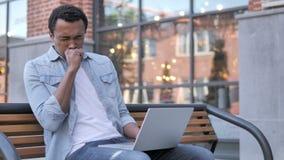 Afrikansk man som hostar, medan arbeta på den utomhus- bärbara datorn stock video