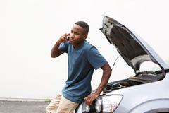 Afrikansk man som kallar på mobiltelefonen för bilservice Fotografering för Bildbyråer