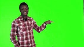 Afrikansk man som pekar på gräsplan lager videofilmer