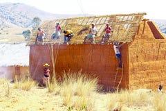 Afrikansk man som reparerar taket i den malagasy byn, Madagascar Arkivfoton