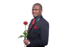 Afrikansk man som rymmer den röda rosen i hand Arkivfoton
