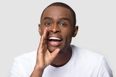 Afrikansk man som rymmer h?nder n?ra munnen som viskar se kameran royaltyfri fotografi