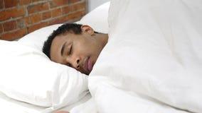 Afrikansk man som sover på sida i säng på natten arkivbild