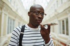 Afrikansk man som stannar till Smartphone royaltyfri foto
