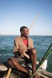 Afrikansk man som stearing ett fartyg nära Tofo Arkivfoto