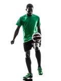 Afrikansk manfotbollspelare som jonglerar konturn Arkivfoto