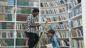 Afrikansk manlig student som söker böcker från hyllorna, medan stå på stege i universitetarkivet för afrikansk kvinnlig arkivfilmer