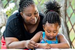 Afrikansk moder som övervakar dotterhandstil royaltyfri foto