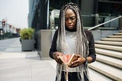 Afrikansk nedstigning som kontrollerar hennes plånbok royaltyfri bild