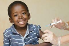 Afrikansk pojke som är lycklig om att få en vaccinering arkivfoto