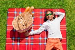 Afrikansk pojke som kopplar av på gräs- äng i sommar Fotografering för Bildbyråer
