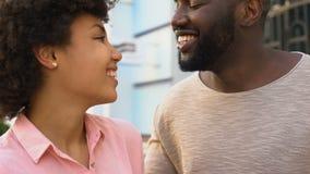 Afrikansk pojkvän som viskar ord av förälskelse till flickvännen, lyckligt le par arkivfilmer