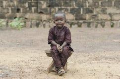 Afrikansk stående för pojkesammanträde utomhus arkivfoton