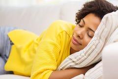 Afrikansk ung kvinna som hemma sover på soffan Arkivfoto