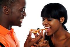 afrikanska härliga par som äter pizza Fotografering för Bildbyråer
