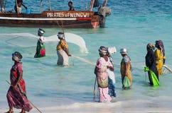 Afrikanska kvinnor från ett fiskeläge som fångar den lilla fisken, förtjänar i havet royaltyfri foto