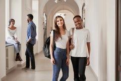 Afrikanska och Caucasian kvinnliga studenter som vilar p? korridoren royaltyfri fotografi