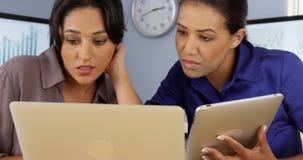 Afrikanska och mexicanska amerikanska affärskvinnor som använder bärbar dator- och minnestavladatoren arkivfoton