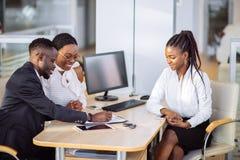 Afrikanska par som får biltangent från återförsäljare i visningslokal och undertecknar avtalet Royaltyfri Bild
