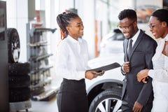 Afrikanska par som får biltangent från återförsäljare i visningslokal och undertecknar avtalet Royaltyfri Fotografi