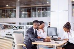 Afrikanska par som får biltangent från återförsäljare i visningslokal och undertecknar avtalet Arkivbild