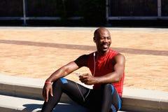 Afrikanska sportar man sammanträde utomhus och lyssna till musik royaltyfri foto