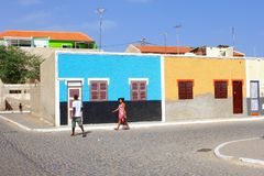 Afrikanskt folk som går färgrika hus för gata, Kap Verde royaltyfria foton