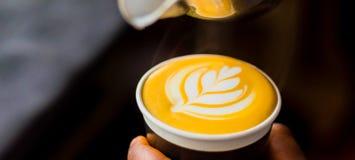 Afrikanskt kaffe Barista som häller en bladform med, mjölkar skum arkivbilder