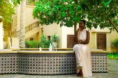 Afrikanskt kvinnasammanträde på springbrunnen arkivbild