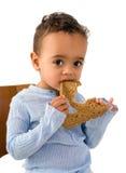 Afrikanskt litet barn som äter bröd arkivbilder