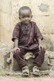 Afrikanskt litet svart pojkesammanträde utomhus med ett ljust leende royaltyfri bild