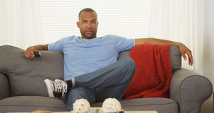 Afrikanskt mansammanträde på hållande ögonen på tv för soffa Arkivfoton