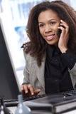 Afro- affärskvinna som är upptagen på arbete Arkivfoton