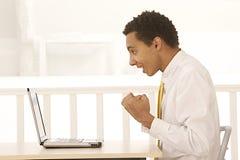 Afro- affärsmanscreamin i glädje framme av hans anteckningsbok Royaltyfri Bild