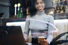 Afro-Américain bouclé dans une veste grise causant avec des amis les invitant pour se réunir en café Photo libre de droits