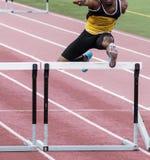 Afro-américain courant la course d'obstacles sur une voie image libre de droits
