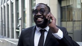Afro-américain dans le costume parlant au-dessus du téléphone portable, sourire radieux, succès photos libres de droits