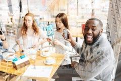 Afro-américain de sourire s'asseyant avec ses amis Image stock