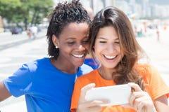 Afro-américain et téléphone de regard caucasien photo stock