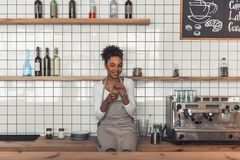 Afro American barista. Beautiful Afro American barista in apron is holding a glass of coffee drink, looking at camera and smiling while sitting on the counter stock photography