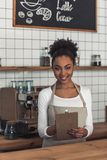 Afro American barista. Beautiful Afro American barista in apron is writing down an order, looking at camera and smiling while standing at bar counter stock photos