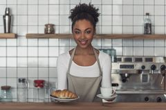Afro American barista. Beautiful Afro American barista in apron is holding a croissant and a cup, looking at camera and smiling while standing at bar counter royalty free stock photo