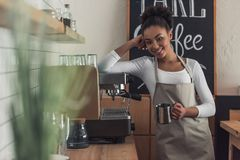 Afro American barista. Beautiful Afro American barista in apron is holding a cup, looking at camera and smiling while leaning on the coffee machine royalty free stock photo
