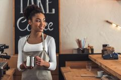 Afro American barista. Beautiful Afro American barista in apron is holding a cup of milk, looking away and smiling while standing near a coffee machine royalty free stock photography