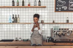 Afro American barista. Beautiful Afro American barista in apron is holding a glass of coffee drink, looking at camera and smiling while sitting on the counter royalty free stock images