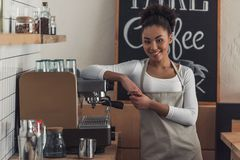 Afro American barista. Beautiful Afro American barista in apron is looking at camera and smiling while leaning on the coffee machine stock photos